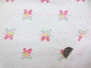 接結ドビーニット 薄いピンク リボンのついた花束に、ちいさな ピンクの音符がならんでいます。 柔らかい肌触りのいい風合いです。